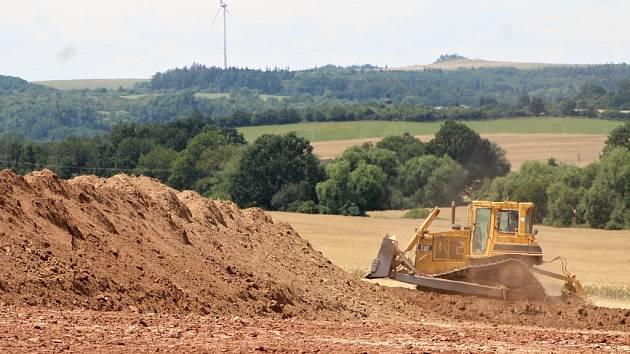 Buldozer při skrývce ornice na stavbě obchvatu Lubence.