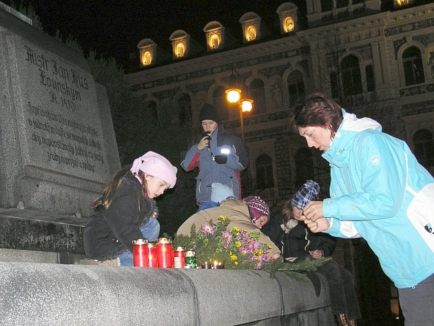 Lidé kladou svíčky k pomníku J. Husa na lounském centrálním náměstí.