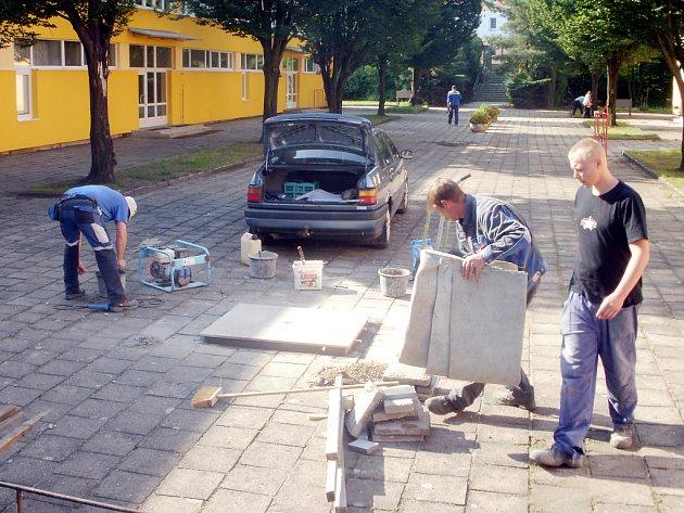 Kameníci připravují novou pamětní desku u školní budovy.