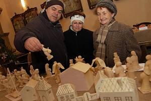 Manželé Petr a Jana Poncarovi ukazují Jiřině Hinkové (vpravo) jeden z vystavených betlémů v kostele svatého Vavřince v Černčicích u Loun.