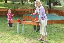 Jako první si všechny herní prvky na novém dětském hřišti v Hnojnicích vyzkoušela tříletá Nellinka Šílová. Na snímku s houpačkou je i její maminka Šárka Šílová.