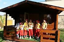 Děti zkoušejí svůj nový zahradní domek.
