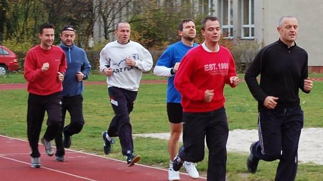 Strážníci Jan Prokop a Petr Gras (zprava) běží na ovále lounské základní školy Přemyslovců.