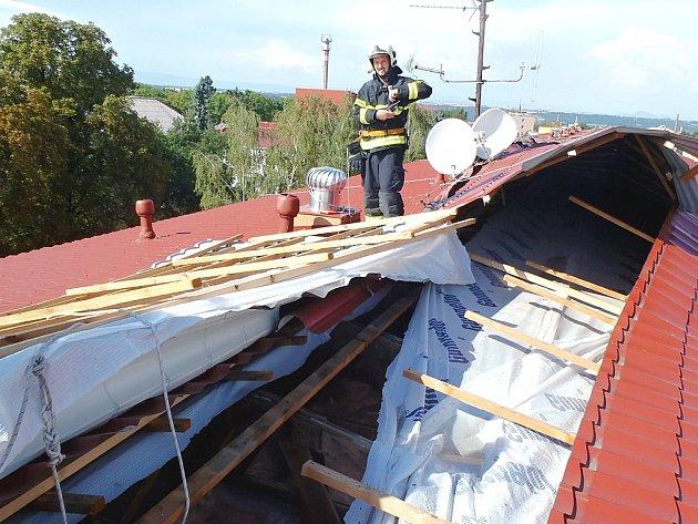 Hasiči zasahují na bytovém domě v Husově ulici, kde část střechy serval vítr