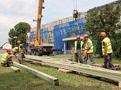 Dělníci připravují vyzvednutí krovů nové střechy, kterou dostane vstupní část polikliniky s lékárnou a chirurgickou ambulancí.
