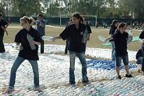 Studenti z podbořanského učiliště skládají slunce z PET lahví na fotbalovém hřišti Tatranu v Podbořanech.