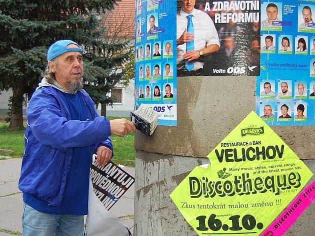 Jaroslav Rosenkranz vylepuje předvolební plakát na Havlíčkově náměstí v Žatci.
