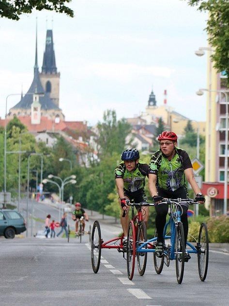 Tricyklisté projíždějí Husovou ulicí
