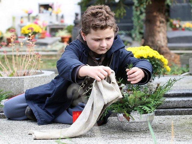 Filip Chaloupka zapaluje svíčku u hrobu svých prarodičů na hřbitově v Žatci.