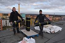 Na panelovém domě v Růžové ulici v Žatci začala oprava větrem poškozené střechy.