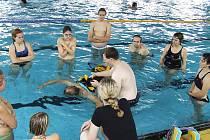 Neslyšící lidé se učí novou dovednost – záchranu tonoucího člověka v bazénu. Výklad podává a ukázky předvádí žatecký záchranář Slavomil Jurnečka (uprostřed).