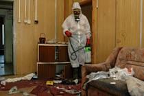 Petr Herblich v ochranném obleku čistí hromady nepořádku v ubytovně v Žatci.