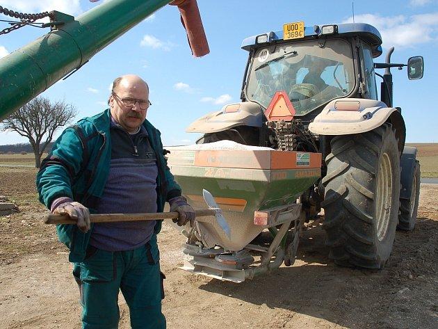 Petr Knotek ze Zemědělské obchodní společnosti Staňkovice dohlíží na sypání ledku do zásobníku za traktorem
