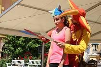 Kejklíř Lukáš Kučera žongluje s noži kolem hlavy Kristýny, dívky  z publika.
