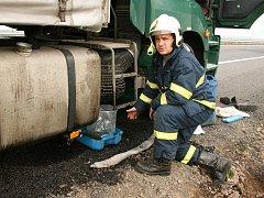 Hasič Roman Paučula ze Žatce kontroluje místo úniku a zachytává unikající naftu