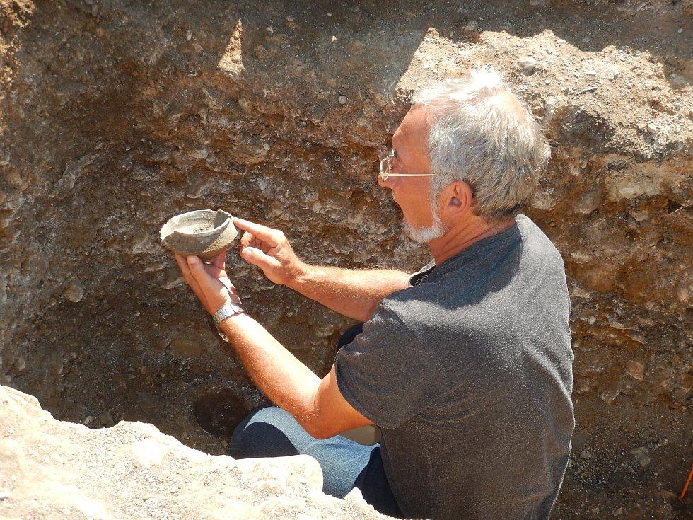 Vedoucí výzkumu Petr Holodňák vyzvedává nádobku zhrobu zdoby stěhování národů.