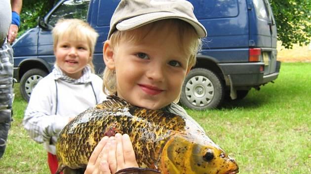 Nejmladší účastník rybářských závodů ve Smolnici Petr Hnilica ze Hříškova s uloveným kaprem koi