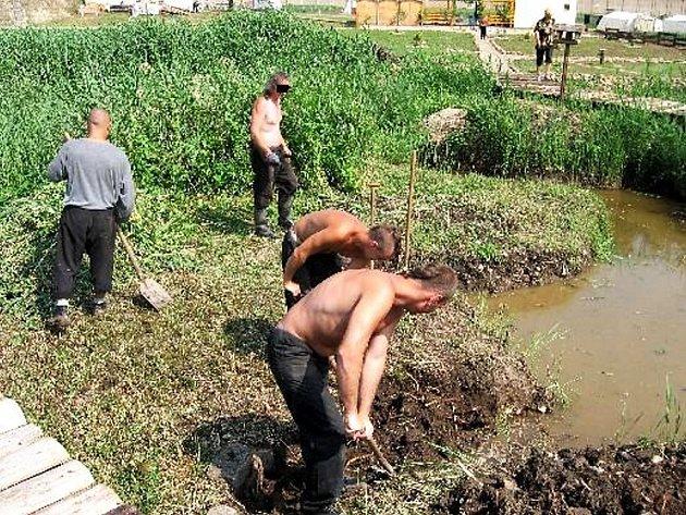 Vězni v Novém Sedle vykopávají jezírko u skalky, kterou vytvořili.