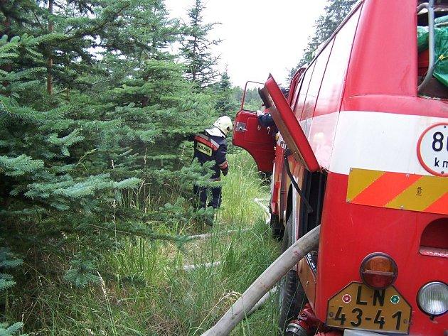 Žatečtí hasiči zasahují při požáru v lese nedaleko Holedeče.