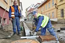 Albert Matys (vlevo) a Jan Schneider ze společnosti Erka pokládají nový obrubník chodníku v Horově ulici v Žatci.