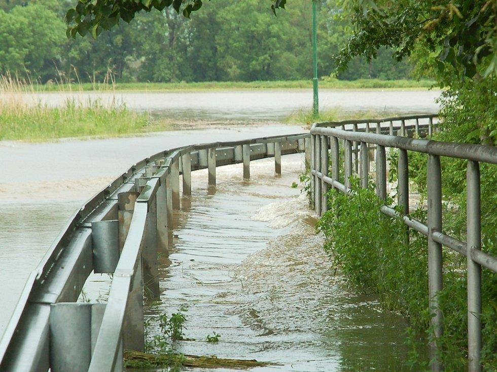 Úterý 4. června 2013. Silnice a chodník mezi Vršovicemi a Černčicemi je kvůli vodě zavřená.