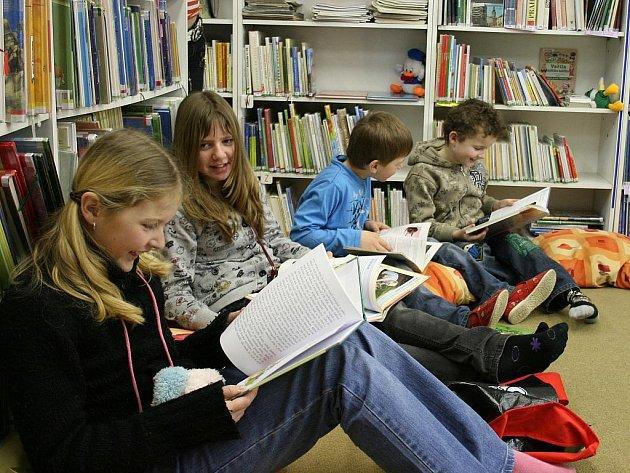 Děti si prohlížejí knihy při návštěvě v Městské knihovně v Lounech