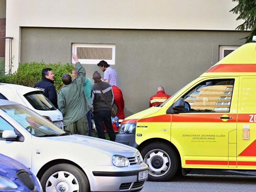 Zdravotníci připravují ženu na transport, policisté debatují o tom, co se stalo