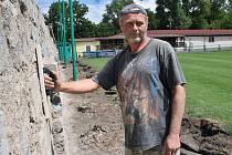 Martin Rampas brousí stěnu u fotbalového hřiště Slavoje Žatec, jejíž fasáda prochází rekonstrukcí.