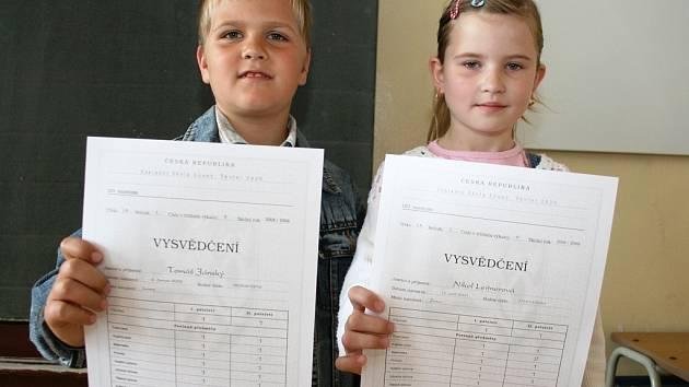 Tomáš Jánský a Nikol Leitnerová z 1.A ukazují čerstvé vysvědčení. Začínají jim prodloužené prázdniny