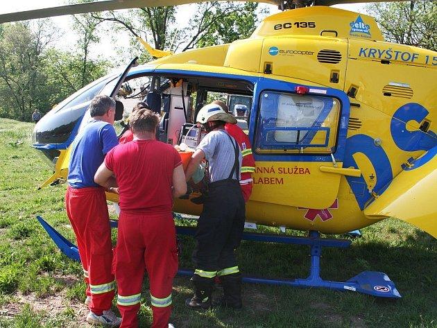 Zdravotníci nakládají zraněného řidiče do helikoptéry.