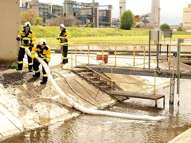 Hasiči přehrazují odtok z nádrže v areálu Elektrárny Počerady sorpčními stěnami.