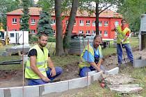 Jakub Vršan, Jan Grus a František Braborec staví novou zpevněnou cestu ve školní zahradě  v areálu MŠ U Jezu v Žatci.