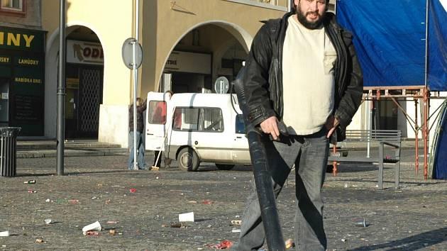 Emil Procházka uklízí střepy od lahví, papíry od pyrotechniky a další nepořádek z plochy žateckého náměstí.