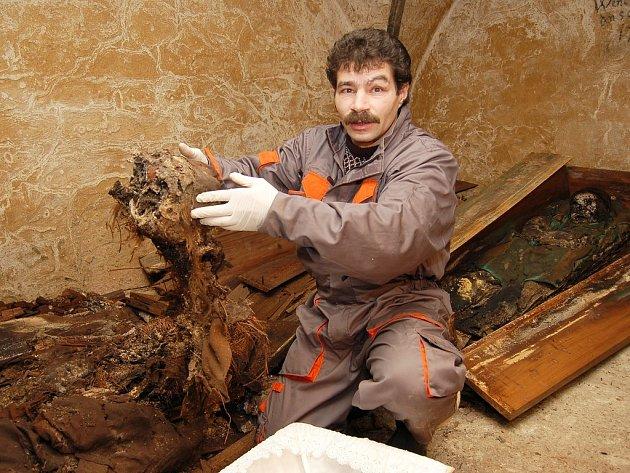 Pastorační asistent Roman Murín vyzvedává ostatky