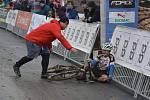 Emotivní fotografie. Tatínek pomáhá synovi po karambolu při závodě.