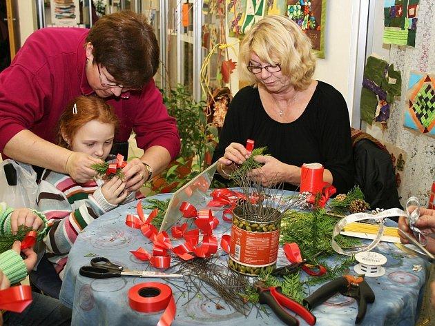 Marie Formánková (vlevo) s dětmi v knihovně vyráběla zajímavou vánoční ozdobu z šišek, větviček jehličnanu a barevných mašliček.