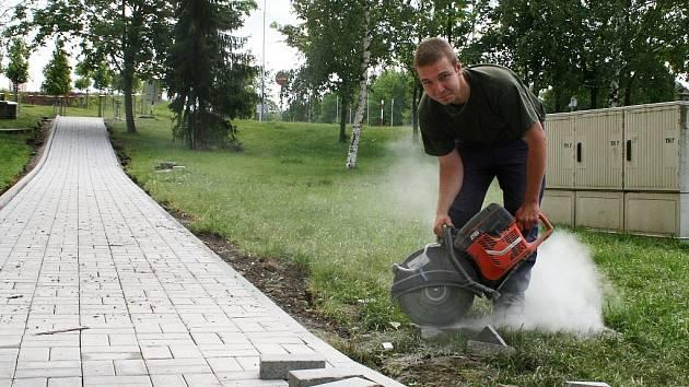 Ladislav Šoufek připravuje dlažbu na vyšlapanou cestičku na sídlišti 28. října u základní školy v Lounech.