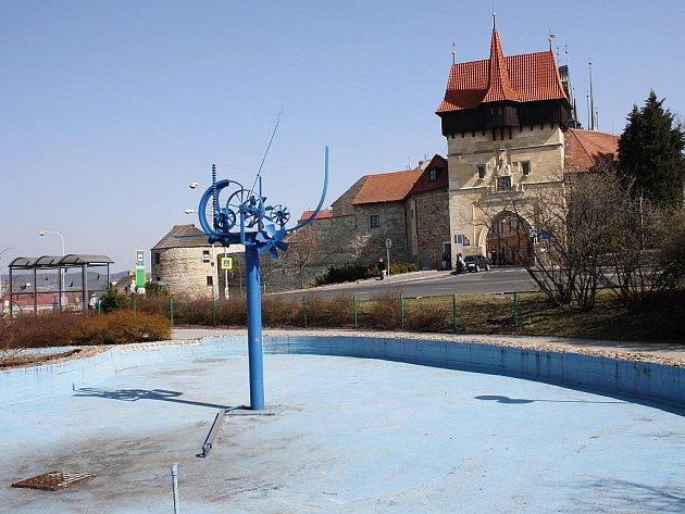 Kašna na Suzdalském náměstí vLounech, vpozadí Žatecká brána