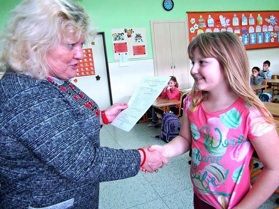 Dvojčata při přebírání prvního vysvědčení v žatecké škole. Na snímku učitelka Jana Piwková s Valentýnkou.