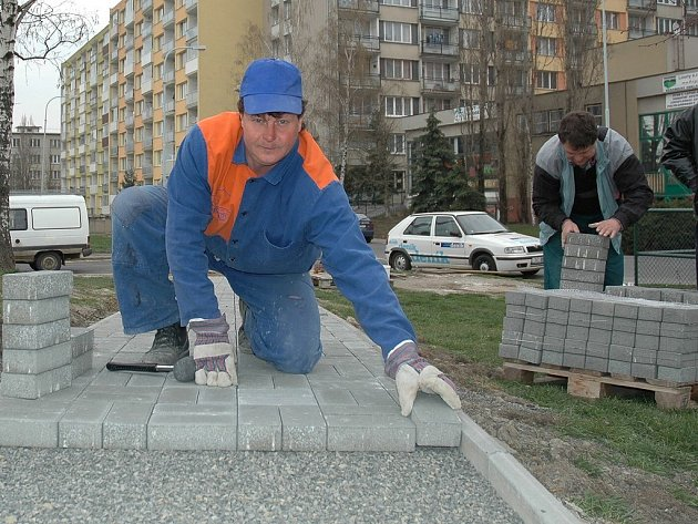 Karel Slach pokládá dlažbu nové cestičky v ulici 17. listopadu v Lounech.