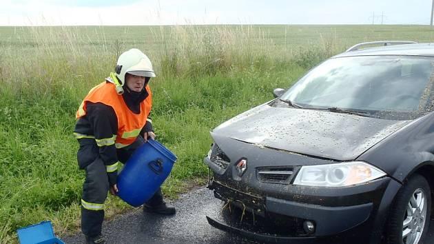 Hasič ze žatecké stanice při nehodě před Měcholupy, likviduje únik provozních látek z auta.