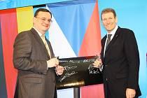 Premiér ČR Petr Nečas a jednatel investorské společnosti Net4Gas Thomas Kleefuss zahajují provoz vysokotlakého plynovodu Gazela. Mezi nimi je symbolický výřez plynovodního potrubí, podepsaný čestnými hosty zahájení provozu.