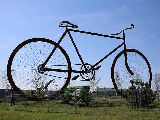 Obří model jízdního kola je k vidění v lounské ulici 5. května. Stojí v areálu společnosti Seko Aerospace