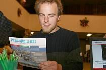 Tomáš Šícha zkoumá nabídku pracovních míst  jedné z firem na setkání v Lounech.