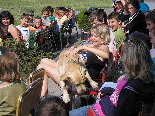 Děti si hrají se psem, se kterým do tábora v Žerotíně přijeli příslušníci vězeňské služby z Nového Sedla.