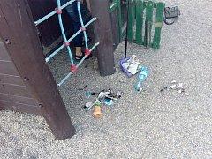 Na dětském hřišti v lounské ulici Skupova se děti snaží rozdělat pod herní sestavou ohýnek.