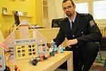 Tomáš Krupička z Okresního ředitelství Policie ČR v Lounech s domky a loutkami, které mají dětem pomoci vyjádřit například určité situace nebo vztahy.
