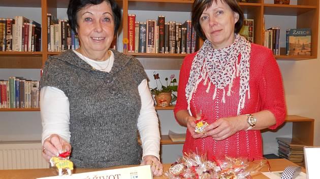 Knihovnice Eva Lerchová (vlevo) a Lenka Styblíková nabízejí sladké perníčky, určené pro návštěvníky žatecké knihovny.