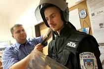 """Aleš Tallowitz a Ondřej Šimůnek z Městské policie Postoloprty zkoušejí protiúderové obleky a další  ochranné pomůcky, které si strážníci vypůjčili od kolegů z mostecké policie před """"návštěvou"""" Dělnické strany."""