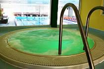 Vířivka pro šest osob je za skleněným průhledem přímo vedle bazénu